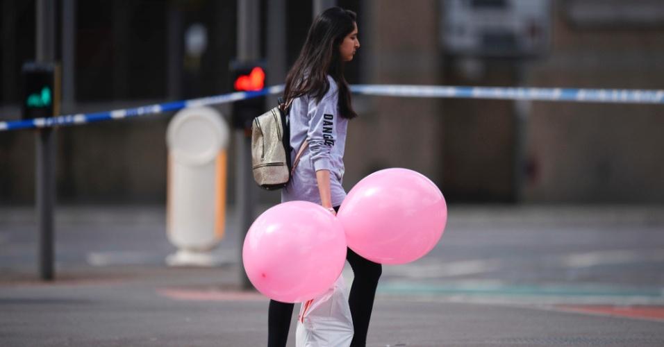 23.mai.2017 - Menina vestindo camiseta da cantora pop Ariana Grande deixa hotel em Manchester (Reino Unido)