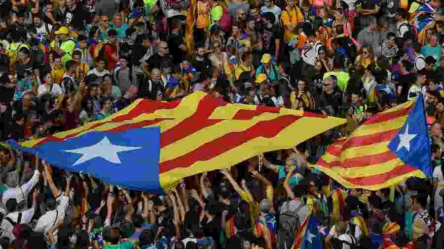 Manifestantes seguram bandeira pró-independência da Catalunha em Barcelona - Lluis Gene/AFP
