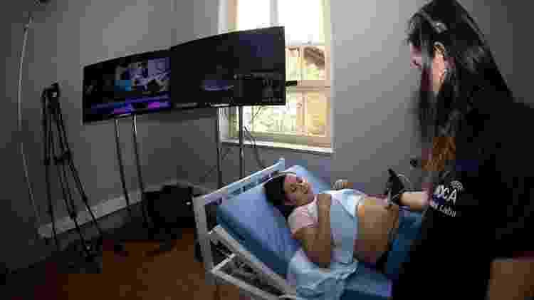 Demonstração de ultrassonografia feita via 5G feita pela Ericsson; médico analisa remotamente enquanto operadora usa luva em barriga da grávida - Renato Saraiva/Pinguim Pictures - Renato Saraiva/Pinguim Pictures
