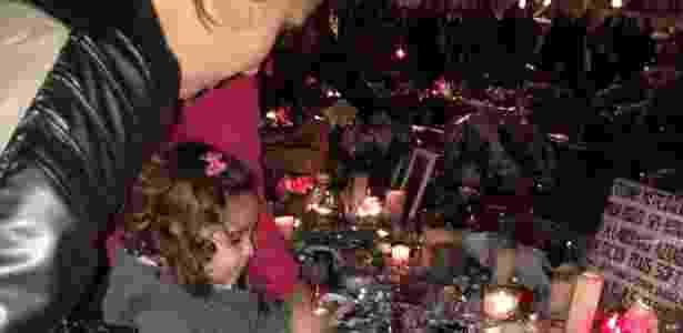 A portuguesa Cíntia de Oliveira ajuda a filha de 2 anos e meio a acender uma vela em homenagem às vítimas, no memorial da praça da República, em Paris - Carolina Vila-Nova/UOL