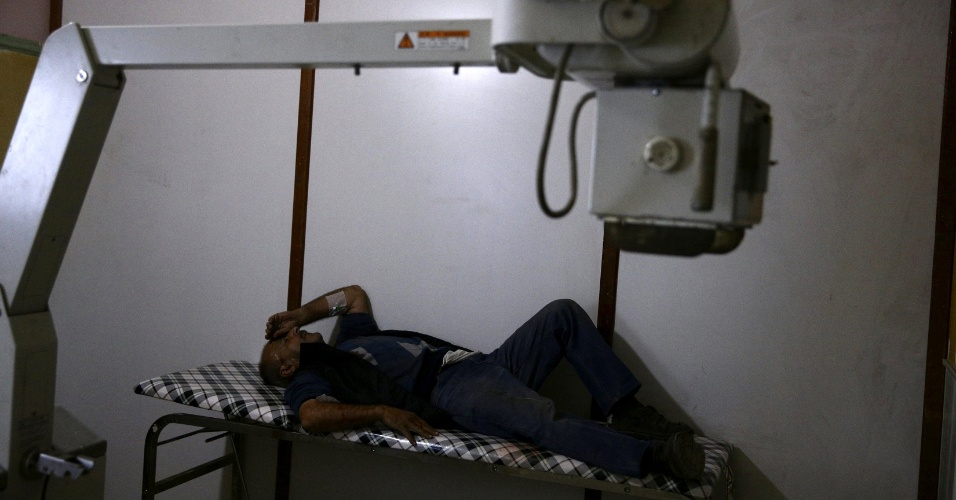 Um dos pacientes do hospital improvisado de Douma descansa no canto de uma das salas do abrigo em meio aos equipamentos usados em exames. A cidade síria é controlada pelos rebeldes e alvo de ataques do Exército de Bashar al-Assad