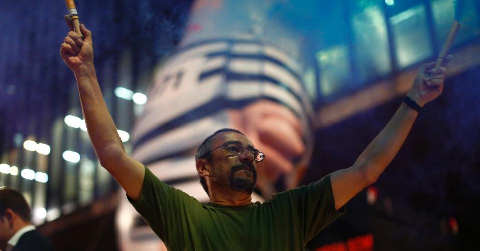 4.mar.2016 - Com pixuleco gigante de Lula ao fundo, homem usa fogos de artifício para festejar a investigação da Operação Lava Jato sobre o ex-presidente Luiz Inácio Lula da Silva (PT), na avenida Paulista, em São Paulo. Proteste ocorre na frente do vão do MASP