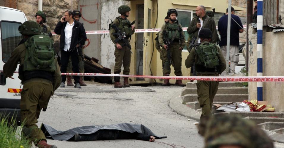24.mar.2016 - Militares israelenses cercam o corpo de palestino morto após ferir um soldado israelense em ataque com faca. Segundo o porta-voz do exército, dois palestinos investiram contra tropas na entrada da colônia israelense de Tal Rumeda, na Cisjordânia ocupada