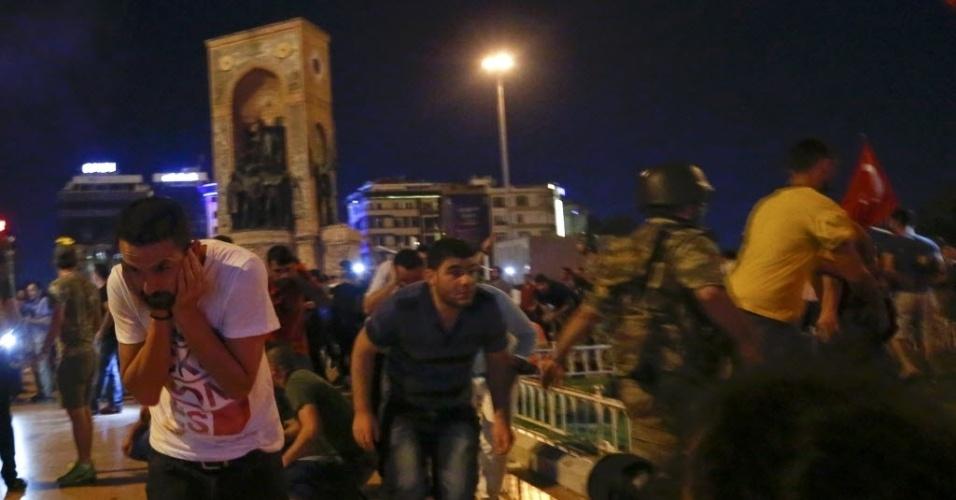 15.jul.2016 - Tiros são disparados e turcos se protegem e fogem da praça Taksim, em Istambul, após tentativa de golpe militar na Turquia. O primeiro-ministro do país, Binali Yildirim, afirmou em rede nacional que há uma tentativa de golpe militar, no entanto, o Exército da Turquia informou que já assumiu o poder