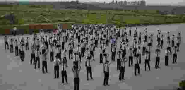 Os estudantes fazem exercícios físicos em grupo  - Suki Kim Image caption  - Suki Kim Image caption