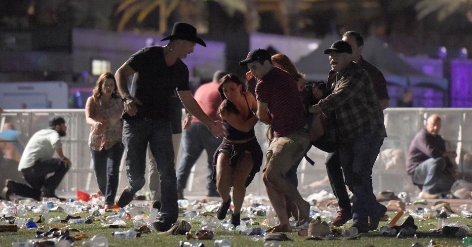 1.out.2017 - Pessoas carregam vítima após tiroteio em festival de música country, em Las Vegas, Nevada