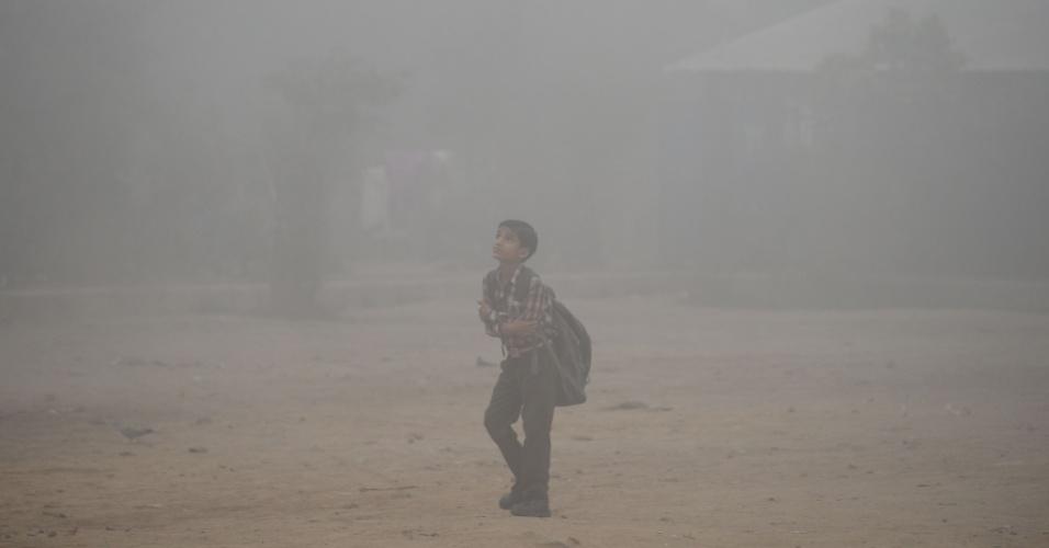 8.nov.2017 - Criança passa por rua envolta por névoa de ar poluído. A associação médica descreveu o efeito da poluição intensa como o equivalente a fumar 50 cigarros em um dia, com sintomas como falta de ar, irritação nos olhos, náusea, fadiga, cefaleia e palpitação