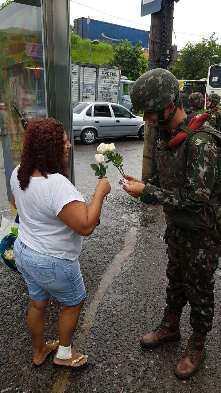 Militar entrega rosa branca para moradora da Vila Kennedy