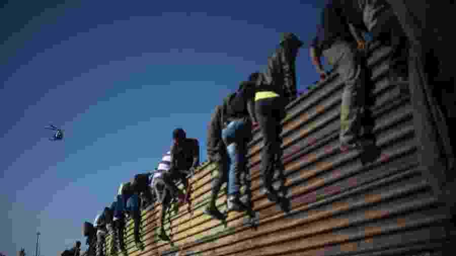 25.nov.18 - Grupo de imigrantes centro-americanos escalam o muro da fronteira entre México e EUA - Pedro Pardo/AFP