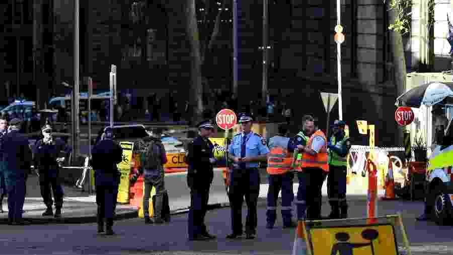 Policiais investigam o local onde um homem esfaqueou uma mulher e perseguiu outras no centro de Sydney, na Austrália - Saeed Khan/AFP