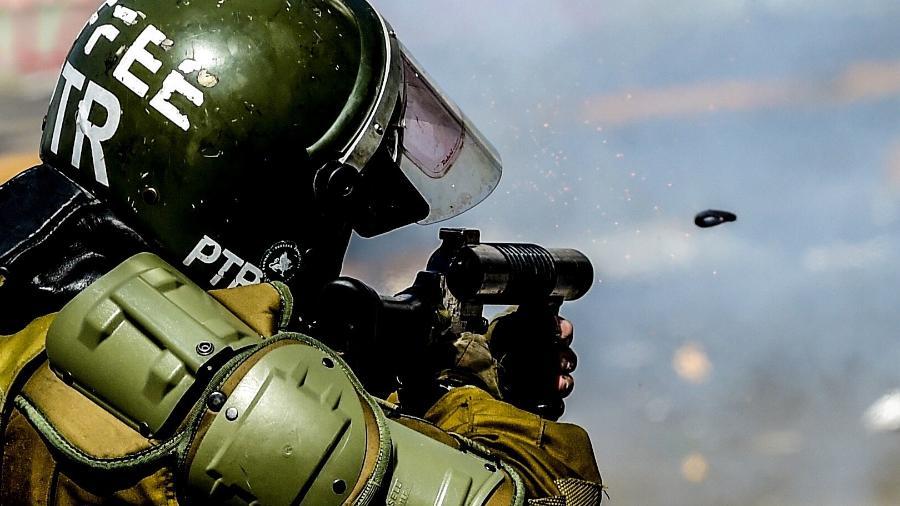 21.out.2019 - Policial atira contra manifestantes durante os protestos em Santiago, no Chile - Martin Bernetti/AFP