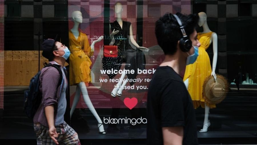 """Pessoas caminham em frente a uma loja da Bloomingdale""""s em Nova York; com a flexibilização da quarentena, local foi recentemente reaberto - Spencer Platt/Getty Images"""