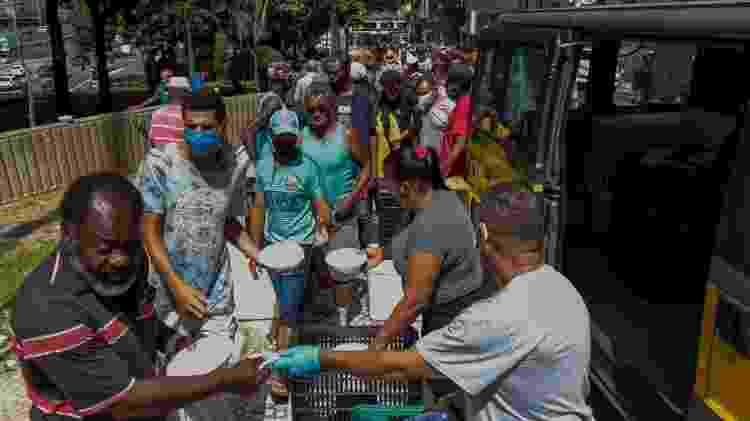 Pessoas em situação de rua recebem marmitas nas ruas de São Paulo, em março de 2021 - Getty Images - Getty Images