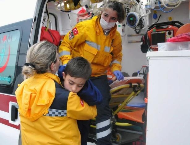 30.jan.2016 - Equipe de resgate ajuda criança que sobreviveu ao naufrágio de um barco com refugiados no mar Egeu - Merit Macit/Xinhua
