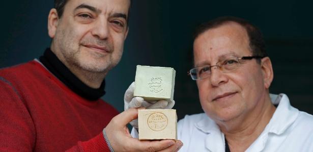 O franco sírio Samir Constantini (esq) e o sírio Hassan Harastani, que fugiu da guerra em Aleppo, com amostras do tradicional sabão em Santeny, na França