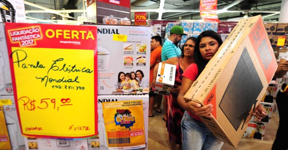 6.jan.2017 - Clientes compram produtos na promoção anual da rede varejista Magazine Luiza na loja da Marginal Tietê, na zona norte de São Paulo, nesta sexta-feira (6). Dezenas passaram a madrugada na fila aguardando a abertura das portas, às 6h