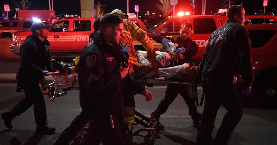 11.mar.2018 -- Paramédicos e policiais de Nova York resgatam vítima do acidente com um helicóptero no East River