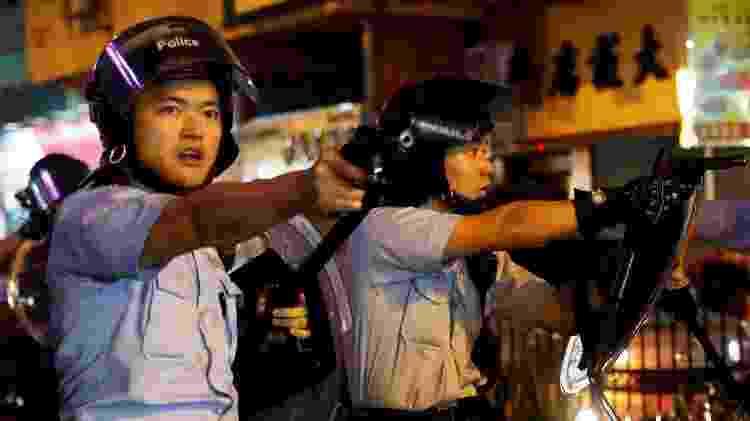 25.ago.2019 - Policiais apontam armas em direção aos manifestantes em Tsuen Wan, Hong Kong - Tyrone Siu/Reuters