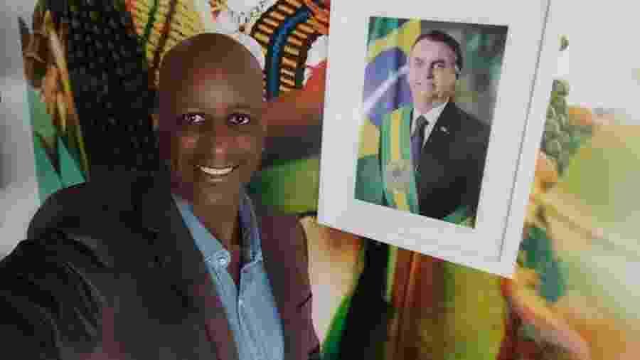 Sérgio Camargo, presidente da Fundação Palmares, posa ao lado de foto do presidente Jair Bolsonaro (sem partido) - Reprodução/Facebook
