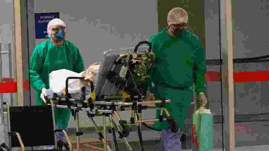 Profissionais da área da saúde levam paciente, de maca, até hospital em Brasília (DF), durante pandemia do novo coronavírus - Mister Shadow/Estadão Conteúdo