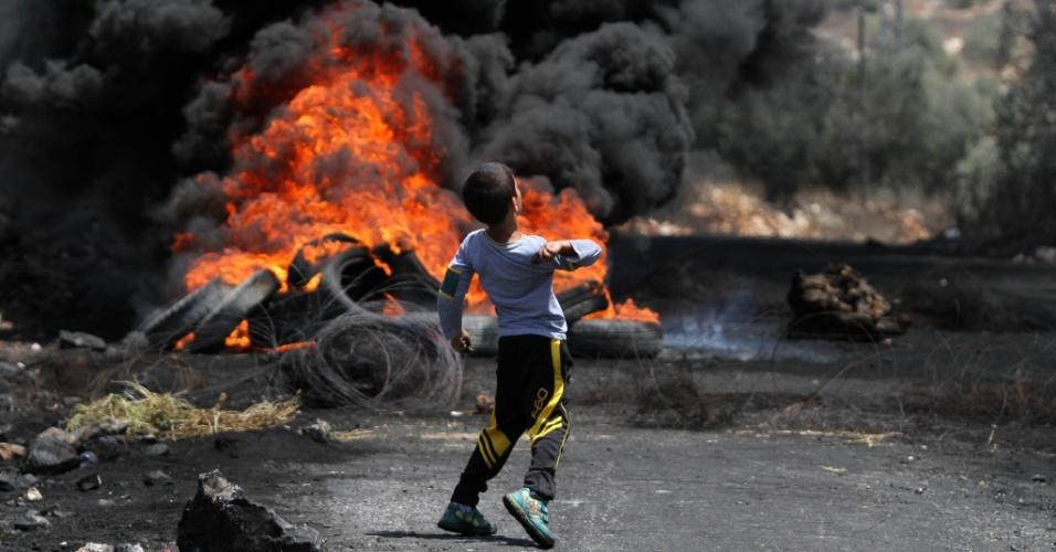 7.ago.2015 - Menino palestino lança uma pedra em direção a soldados israelenses durante protesto contra a expansão de assentamentos judeus, no vilarejo de Kufr Qadoom, próximo à cidade cisjordana de Naplusa