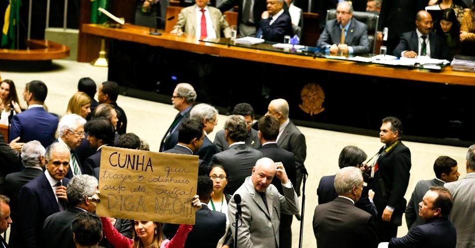"""28.out.2015 - A deputada federal Clarissa Garotinho (PR-RJ) ergue no plenário um cartaz com os dizeres: """"Cunha quer trazer o dinheiro sujo da Suíça. Diga Não!?. Antes, Garotinha havia discutido com o presidente da câmara dep. Eduardo Cunha (PMDB-RJ) afirmando que ele não tem dado a palavra a ela nas sessões e o chamou de ditador"""