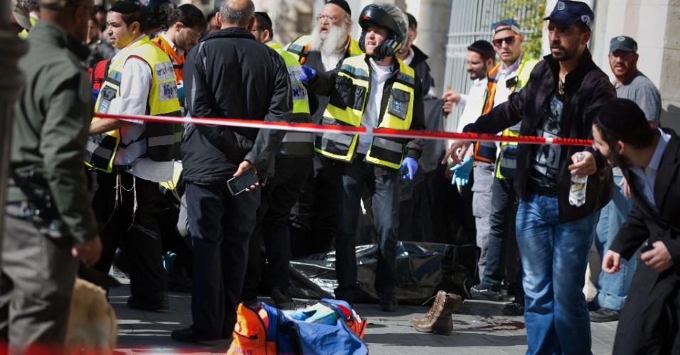 23.nov.2015 - Uma adolescente palestina foi morta e outra ficou ferida pela polícia israelense após atacarem um homem no principal mercado da parte oeste de Jerusalém, em Israel. Um policial que estava no local atirou contra as duas. Na foto, o corpo coberto de uma das jovens é cercado por judeus ultraortodoxos e pelas forças de segurança israelenses