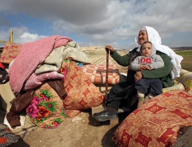 Palestina que teve a casa demolida pelo Exército de Israel senta-se ao lado dos objetos pessoais que restaram, em Hebron, na Cisjordânia