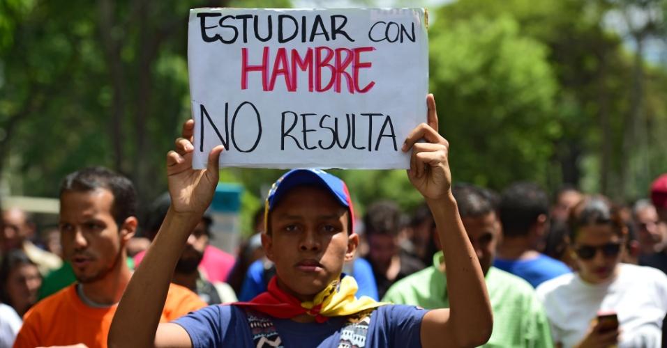 """26.mai.2016 - Estudantes universitários protestam contra as políticas públicas do governo Nicolás Maduro, em Caracas, na Venezuela. No cartaz, lê-se """"estudar com fome não dá resultado"""". O país passa por uma grave crise de abastecimento de alimentos da cesta básica"""