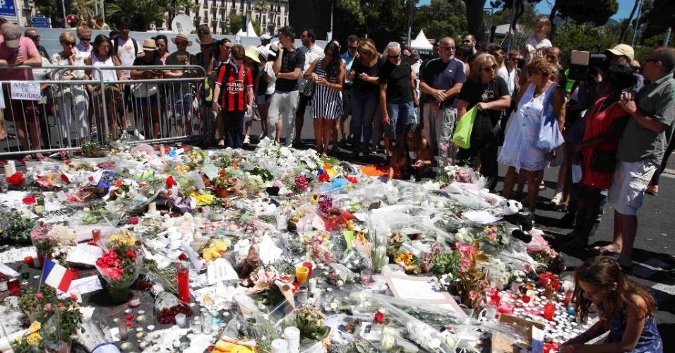 16.jul.2016 - Pessoas se reúnem neste sábado (16) em torno de flores colocadas em homenagem às vítimas do ataque realizado por um cidadão franco-tunisiano em Nice, na França, na última quinta-feira (14)