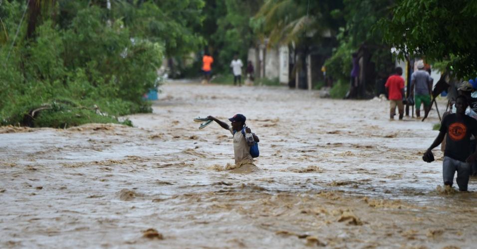 5.out.2016 - Homem tenta atravessar o rio Rouyonne na comuna de Leogane, em Porto Príncipe, capital do Haiti, que transbordou com a passagem do furacão Matthew