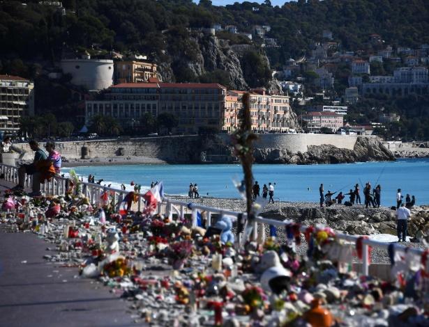 Franceses sentam ao lado de velas, flores e bandeiras colocados na orla da praia em homenagem às vítimas do ataque terrorista em Nice, na França, em 14 de julho