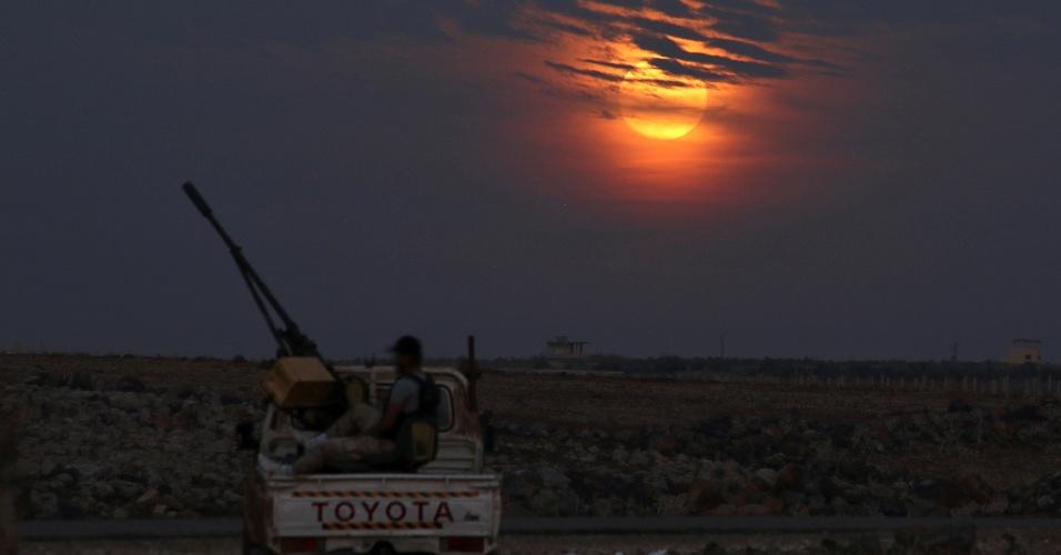 Soldado do Exército Livre da Síria em guarda a oeste da cidade de Dael, na Síria, sob o luar da superlua