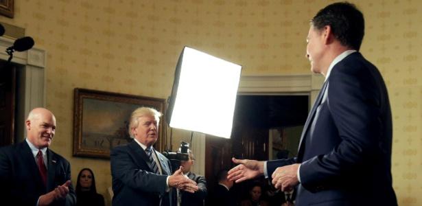 22.jan.2017 - James Comey, então diretor do FBI, cumprimenta Donald Trump em evento no Salão Azul da Casa Branca, dois dias após a posse do presidente