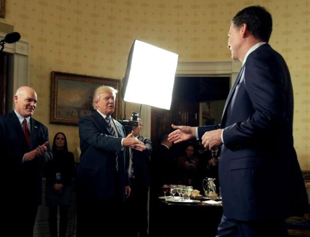 James Comey estende a mão a Donald Trump assim que este o vê e o chama, no Salão Azul da Casa Branca, em evento no qual o então diretor do FBI, segundo um amigo, tentava se esquivar do presidente