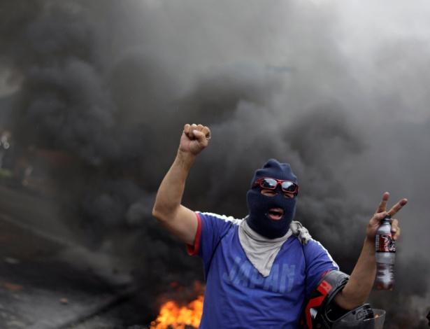 Opositor durante um protesto que ocorreu depois que a Organização dos Estados Americanos rejeitou uma declaração de vitória para o presidente hondurenho, Juan Orlando Hernandez, em Tegucigalpa - JORGE CABRERA/REUTERS