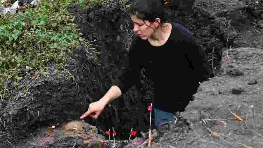 Em foto de 28 de agosto de 2019, mulher aponta ossada parcialmente desenterrada em batalhão do Exército uruguaio que funcionou como centro de detenção e tortura em Montevidéu; restos mortais pertencem a Eduardo Bleier, desaparecido em 1975 - Pablo Porciuncula Brune/AFP