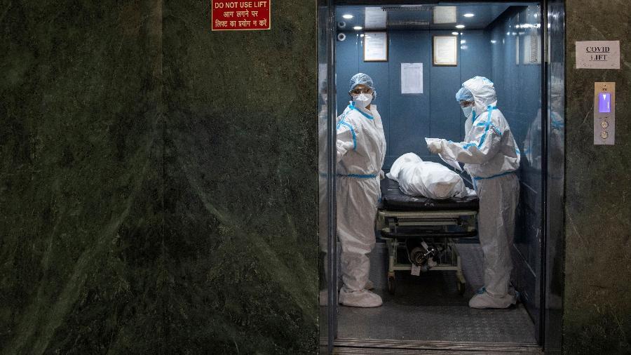 Funcionários removem da UTI o corpo de um paciente que morreu de complicações relacionadas à covid-19 no Holy Family Hospital em Nova Déli, Índia - Danish Siddiqui/Reuters