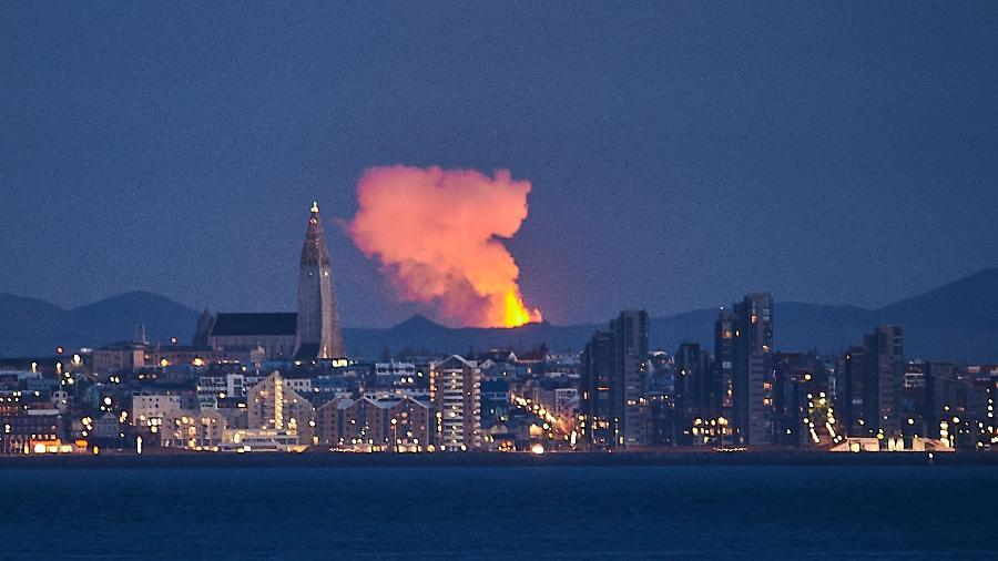 Foto de arquivo tirada em 5 de maio mostra o horizonte da capital da Islândia, Reykjavik, com o brilho da lava saindo de uma fissura do vulcão - Halldor KOLBEINS / AFP