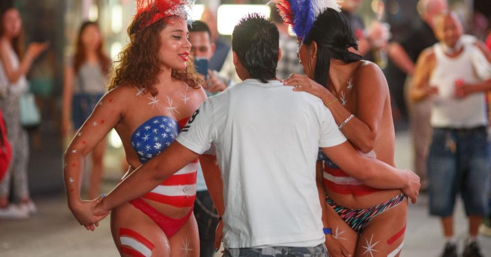 22.ago.2015 - Mulheres de topless e pintura corporal abordam turista nesta sexta-feira (21) na Time Square, em Nova York