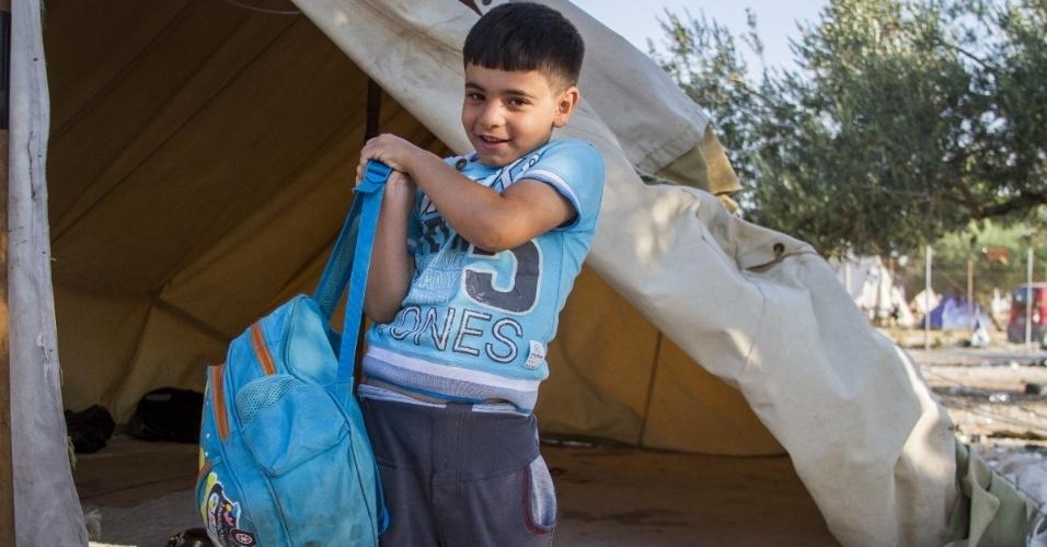 O sírio Omran, 6, sorri ao dizer que está partindo com a sua família de cinco pessoas para a Alemanha, onde vai viver com parentes. Ele conta que os pais disseram que viajariam por florestas e por isso precisariam carregar em sua mochila azul curativos para possíveis feridas e arranhões