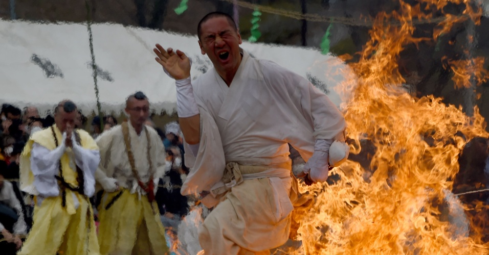 """6.mar.2016 - Fiel budista corre descalço sobre brasas no templo Fudoji durante a cerimônia do """"Hi-Watari"""" (caminhada sobre fogo), em celebração da chegada da Primavera no hemisfério norte, na cidade japonesa de Nagatoro. Centenas de seguidores do budismo asceta participam da cerimônia para purificar o corpo e a mente"""
