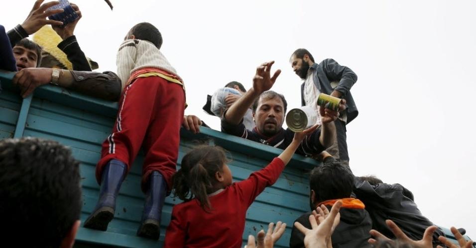 26.mar.2016 - Voluntários distribuem donativos entre adultos e crianças que vivem em um acampamento improvisado para refugiados na fronteira entre Grécia e Macedônia