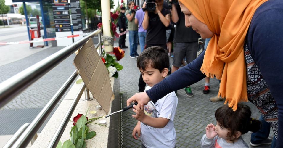 23.jul.2016 - Mulher leva os filhos para acender velas próximo ao shopping onde houve um ataque, em Munique, que terminou com a morte de dez pessoas. Segundo a polícia, o atirador, um germânico-iraniano de 18 anos, matou nove pessoas antes de se matar