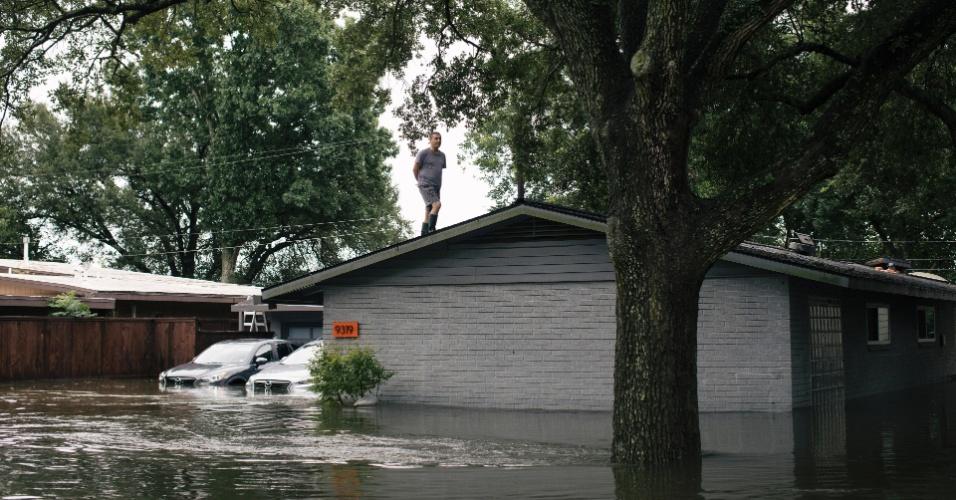 27.ago.2017 - Homem observa enchente do telhado de uma casa na região de Meyerland, em Houston, após a passagem da tempestade Harvey