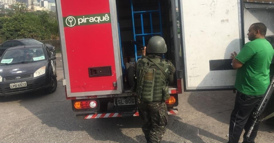 27.out.2017 - Militar aponta fuzil para interior de um veículo de carga após abordagem a um motorista que havia acabado de descarregar alimentos em uma padaria no morro do São Carlos