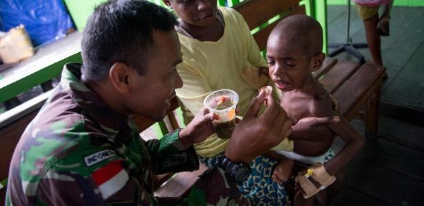 Membro do Exército da Indonésia atende uma criança no hospital em Agats, em Papua