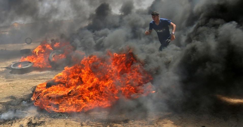 14.mai.2018 - Homem palestino caminha em meio a fumaça de pneus em chamas durante confronto com forças de Israel na cidade de Khan Yunis, na Faixa de Gaza. Palestinos protestam contra a inauguração da embaixada dos EUA em Jerusalém
