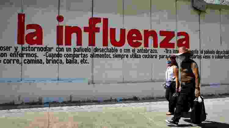 Pessoas andando em frente a mural no México, em 2009 - Getty Images - Getty Images
