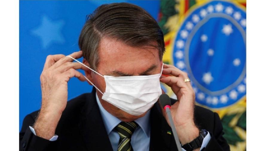 Bolsonaro cobre os olhos com máscara  - Adriano Machado/Reuters